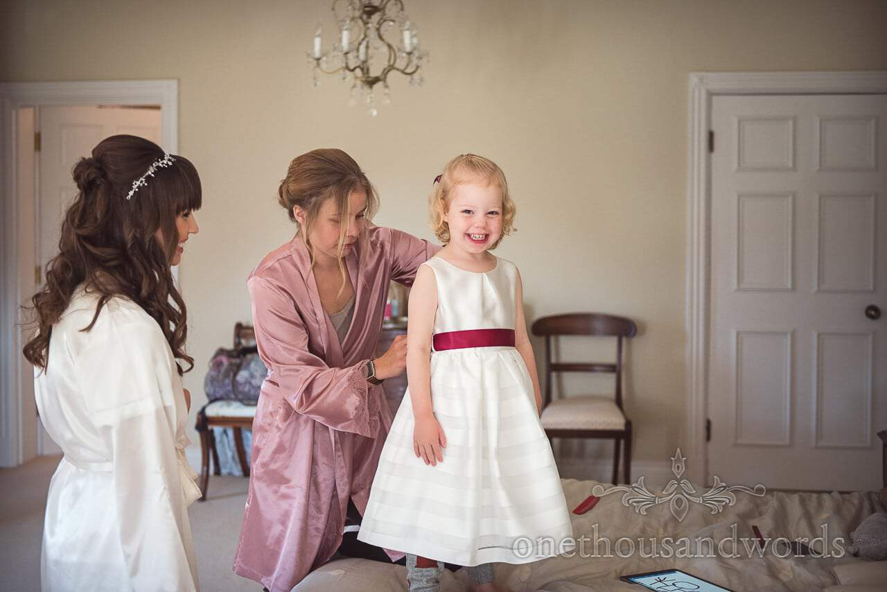 Cute wedding flower girl puts on white dress with deep red ribbon
