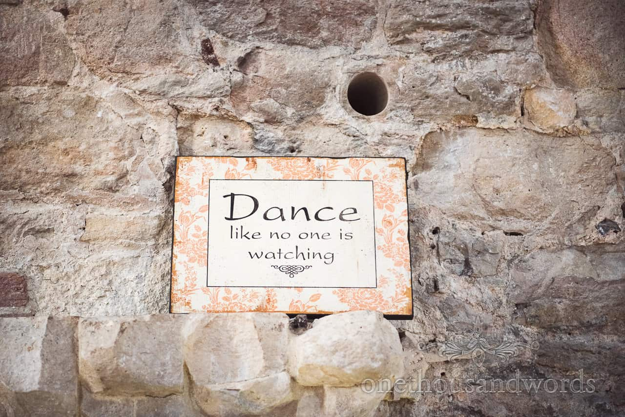 Dance like no one is watching wedding sign on castle stone wall at Lulworth wedding