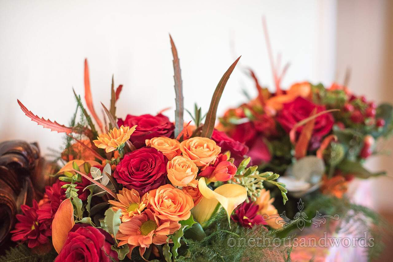 Deep red and orange wedding bouquets with green and red foliage