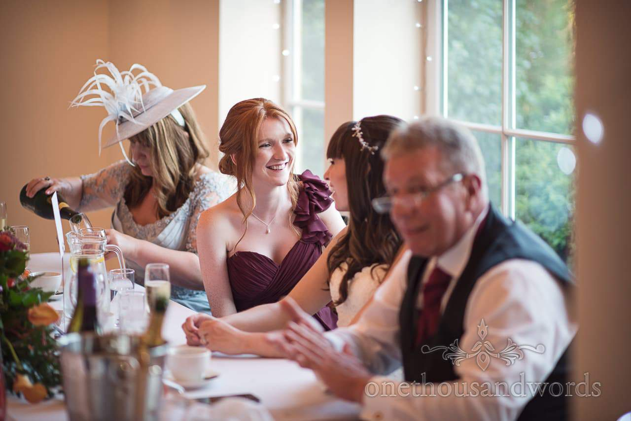Documentary wedding photograph of bridesmaid laughing with bride