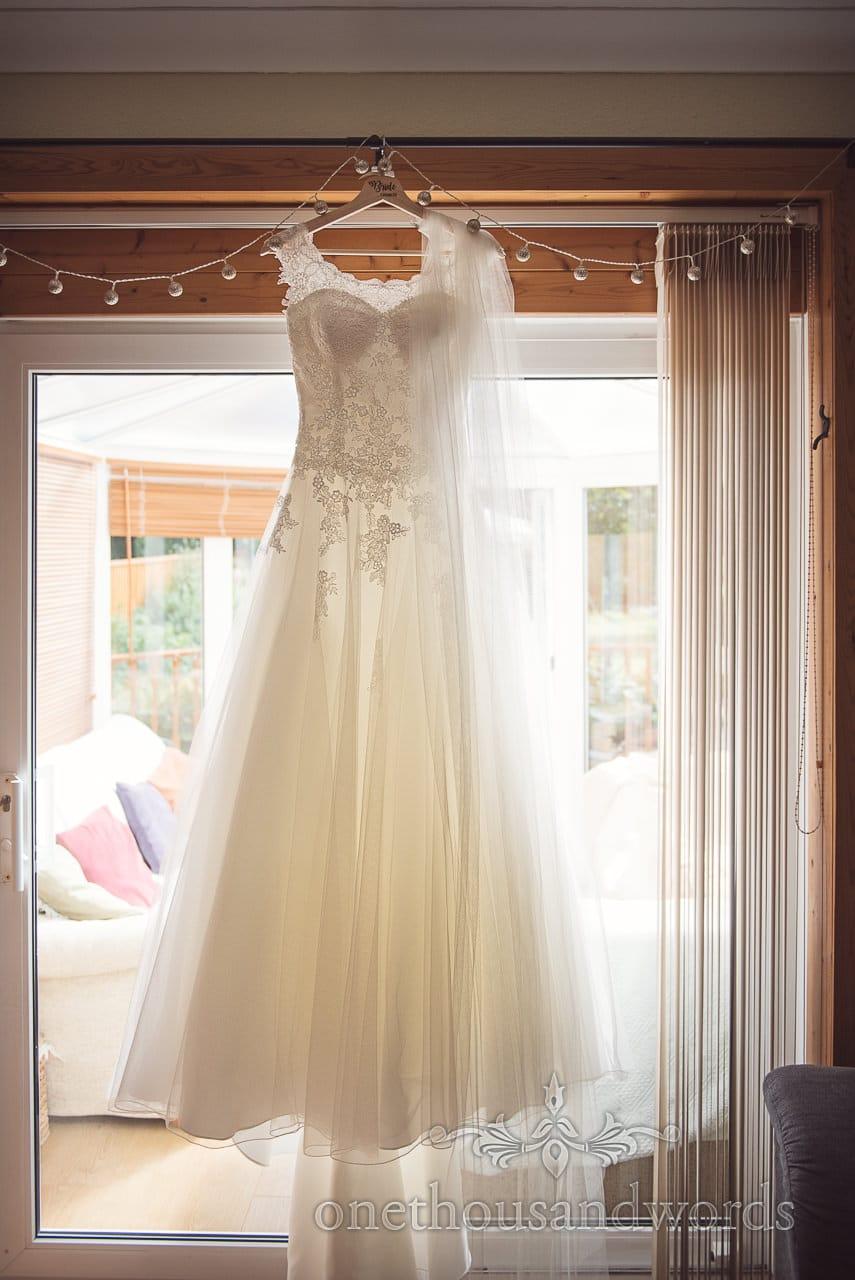 Dress hangs in window before woodland Lulworth Castle wedding