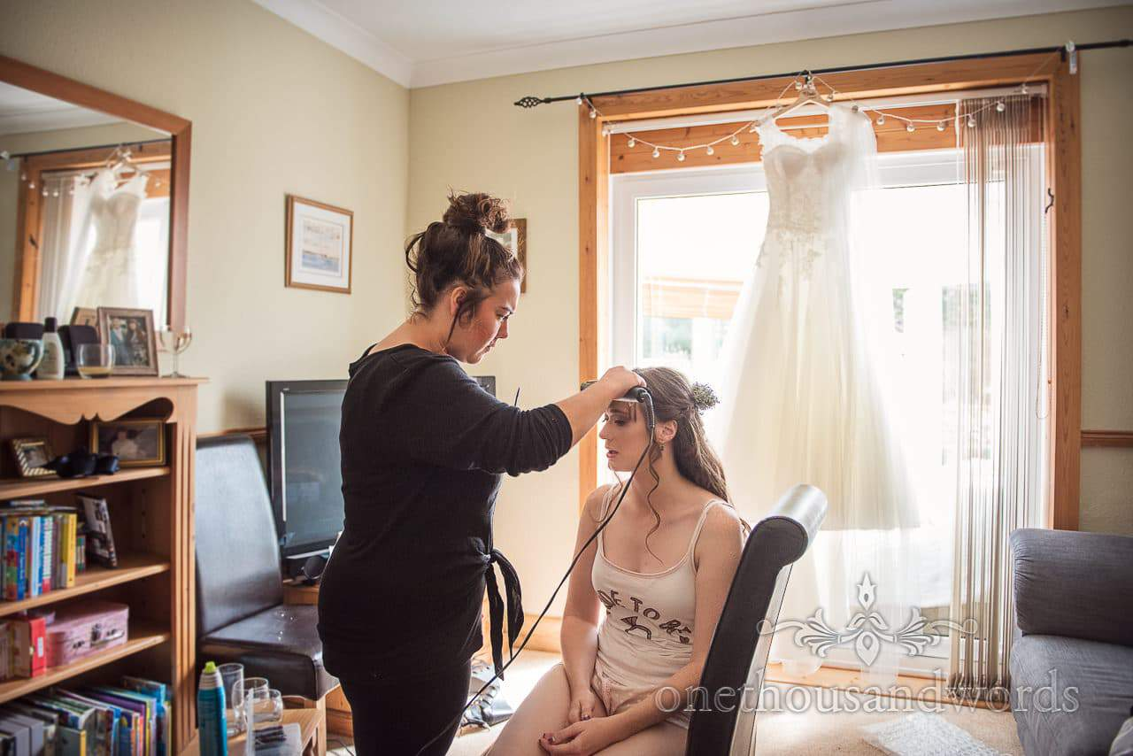 Dress hangs in window while hair is styled before woodland Lulworth Castle wedding