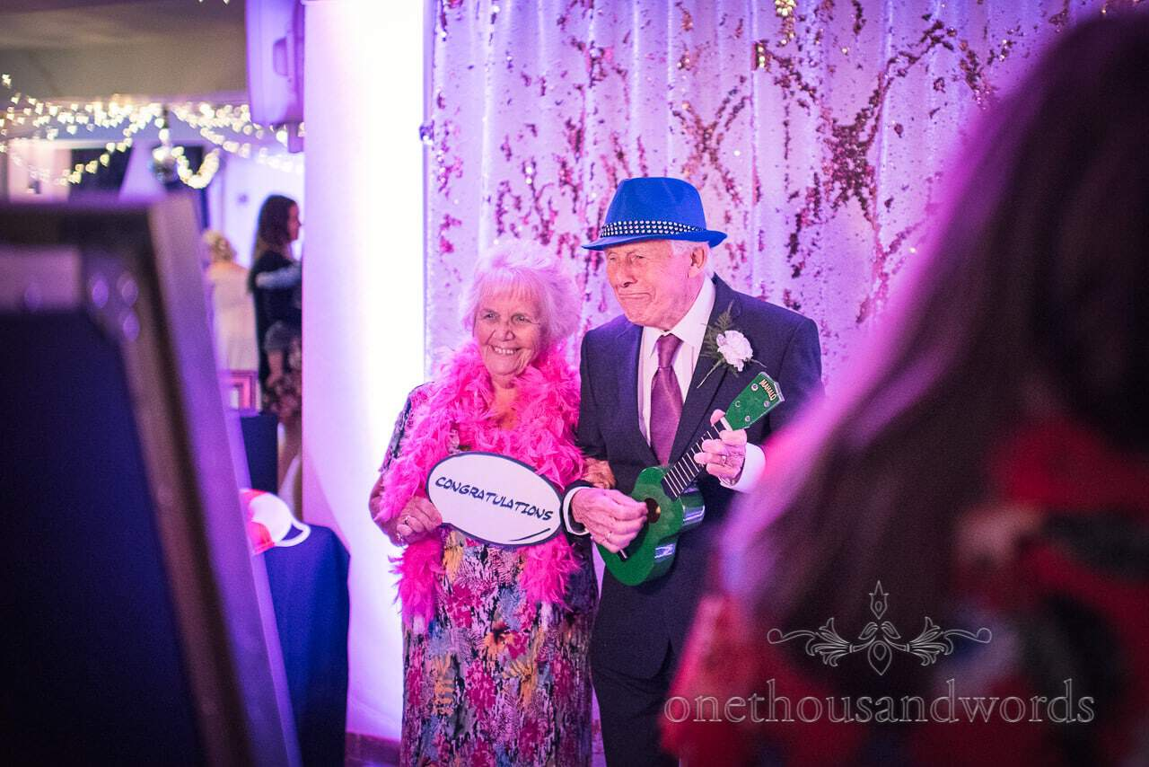 Elderly couple in photobooth with funny props at The Italian Villa Wedding venue