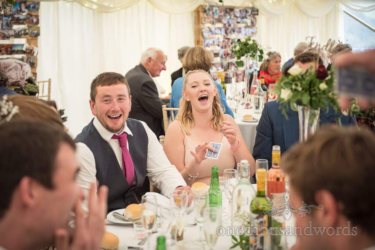 Farm marquee wedding photo of guest being entertained by magician