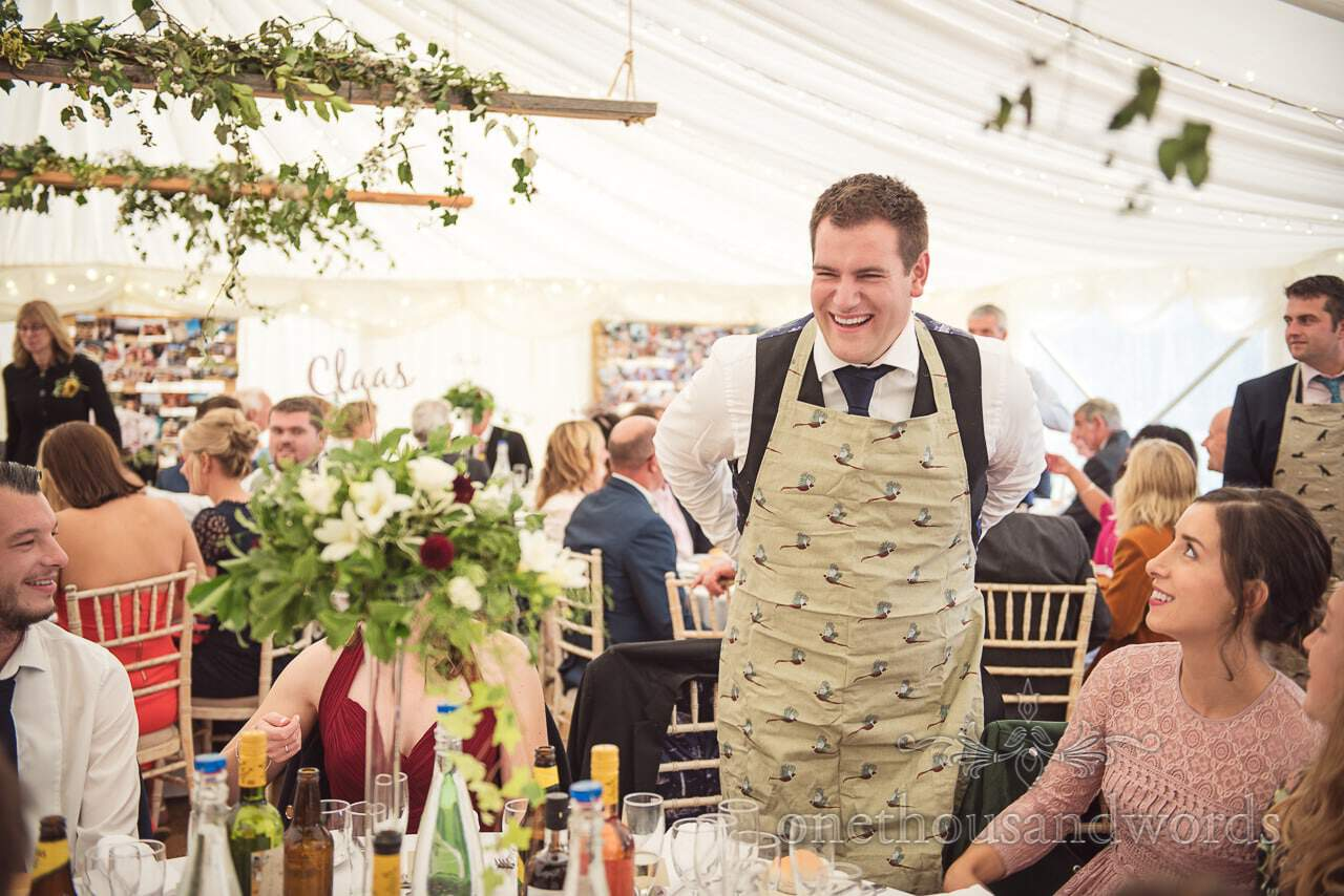 Farm marquee wedding photo of guest ready to carve beef joint