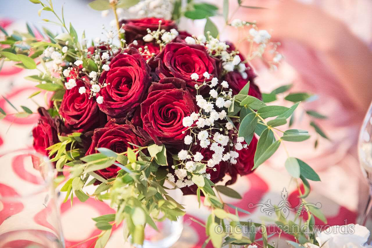 Farm marquee wedding photographs of deep red rose bouquet