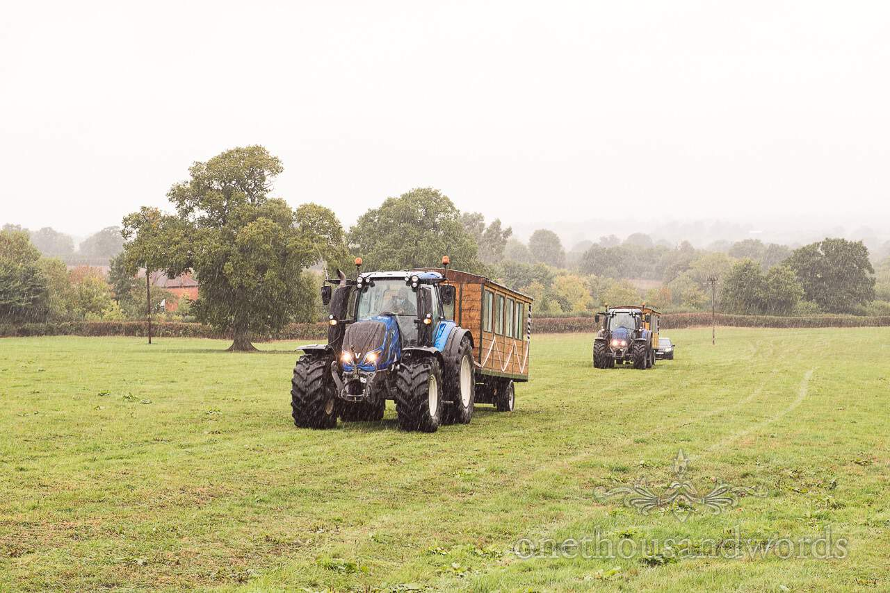 Farm marquee wedding photographs of guests arriving by tractor and trailer
