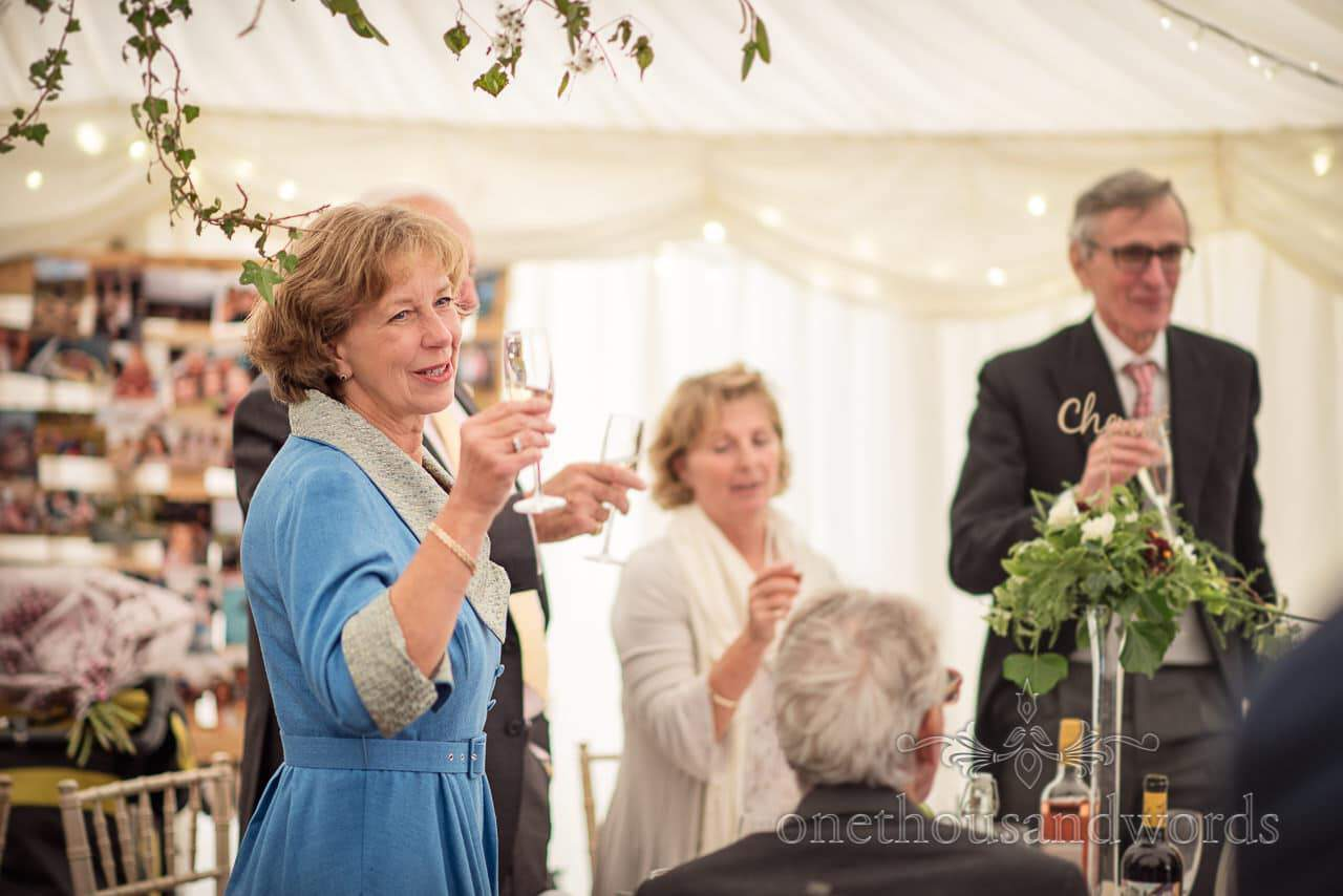 Farm marquee wedding photos of guest raising glass to toast