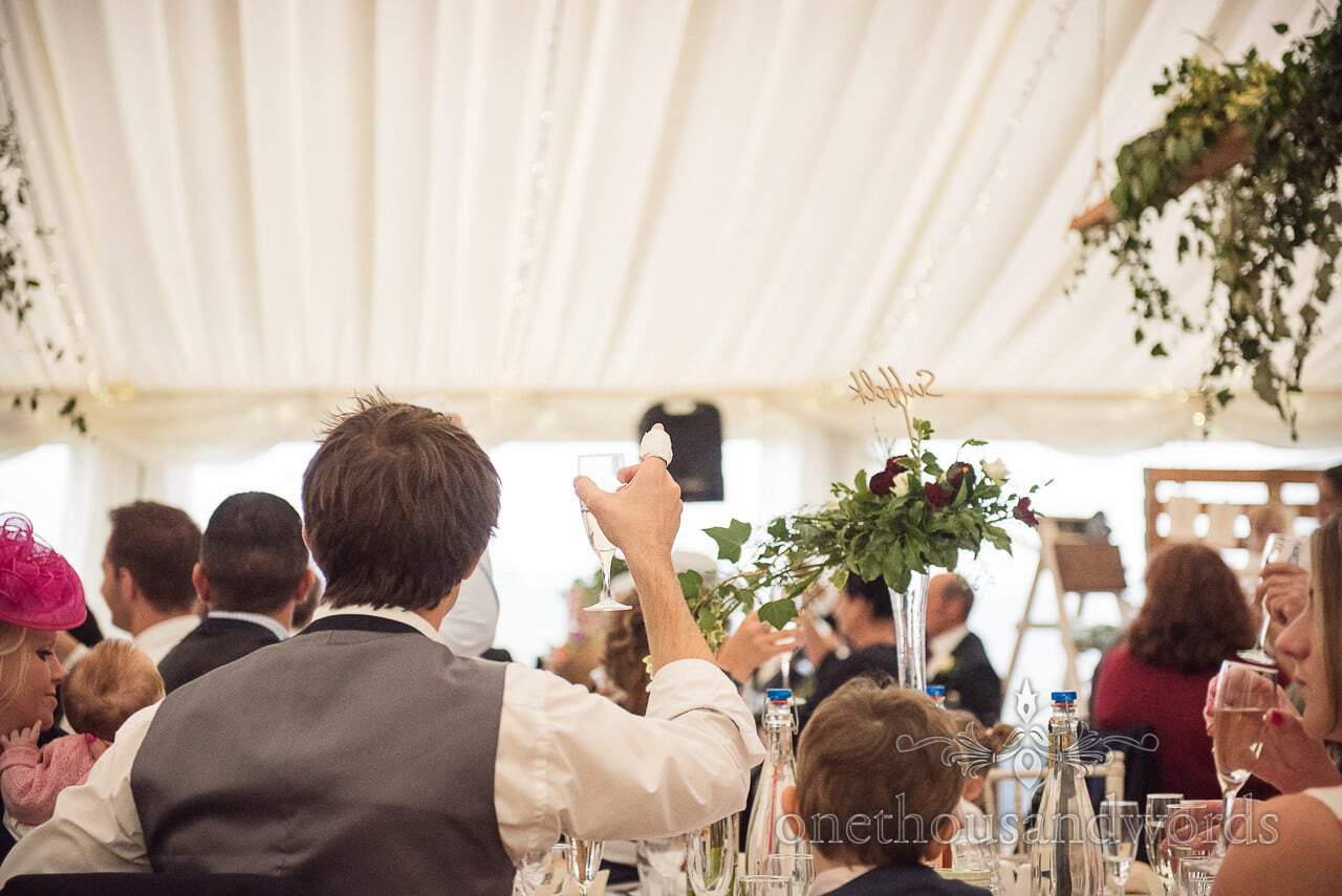 Farm marquee wedding photos of guest with finger injury raised glass to toast