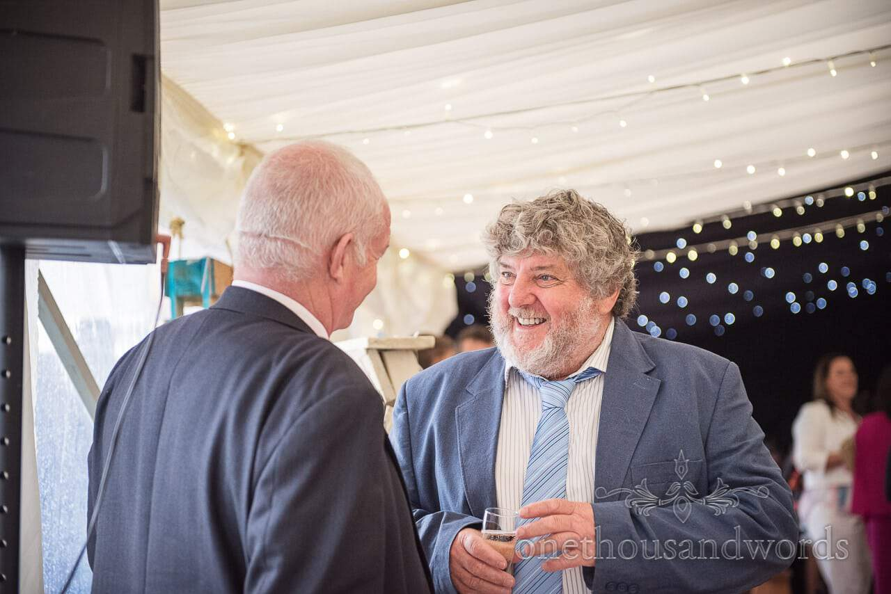 Farm marquee wedding photos of guests enjoying drinks reception