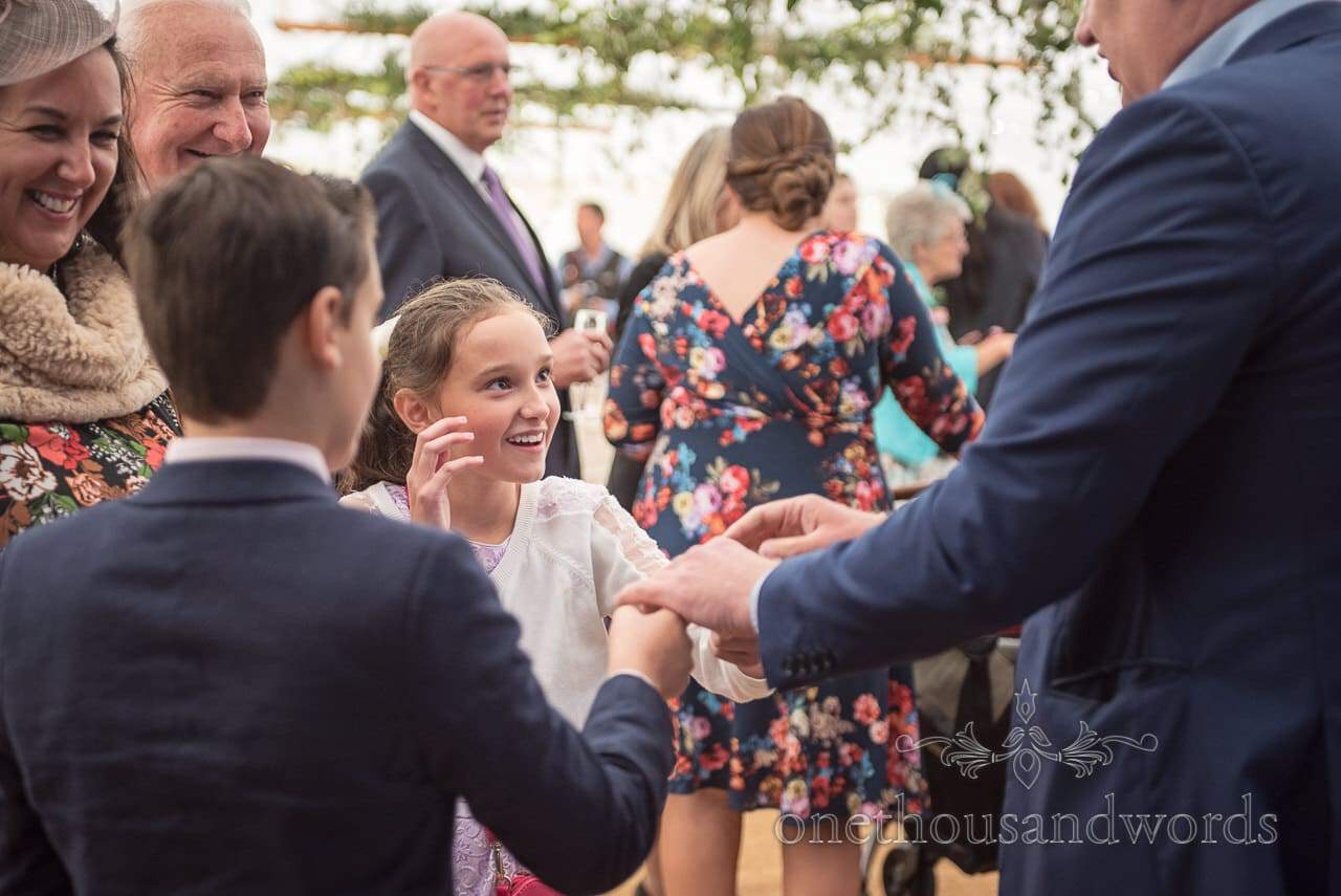 Farm marquee wedding photos of magician entertaining young guests