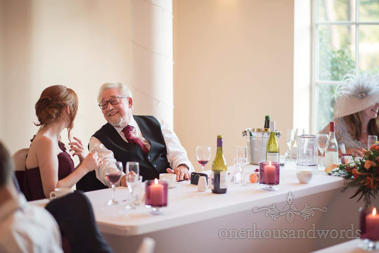 Father of the bride chats with bridesmaid at Wedding breakfast