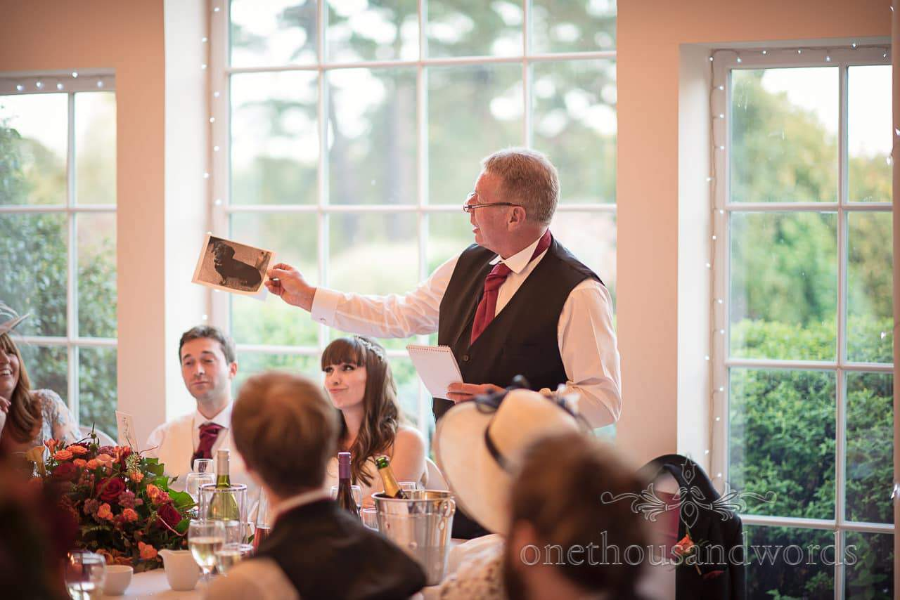 Father of the bride holds up picture of pet dog during wedding speech