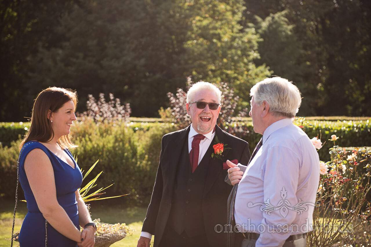 Father of the bride laughing in the sun shine at Hethfelton House
