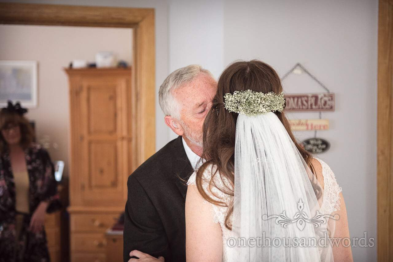 Father of the bride and bride embrace on morning of woodland Lulworth Castle wedding