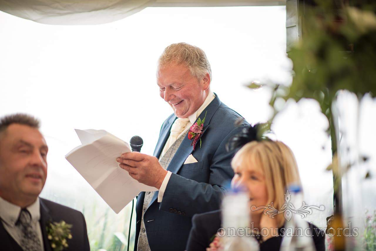 Father of the bride delivers speech during farm marquee wedding reception