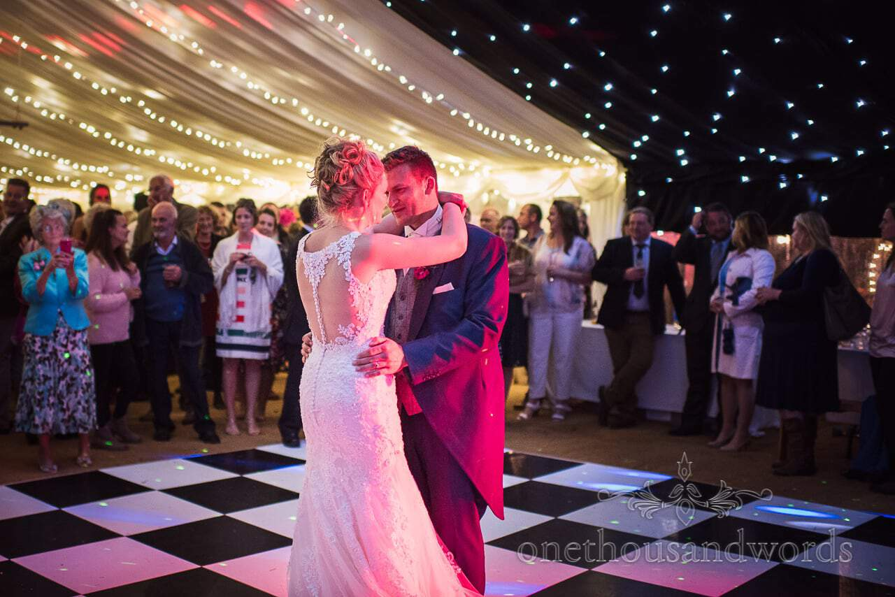 First dance on checker board dance floor watched by wedding guests