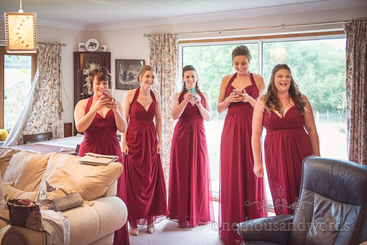 Five bridesmaids in deep red dresses see bride in dress