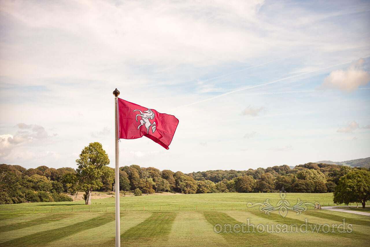 Flag with white horse of Kent flies at woodland Lulworth Castle wedding