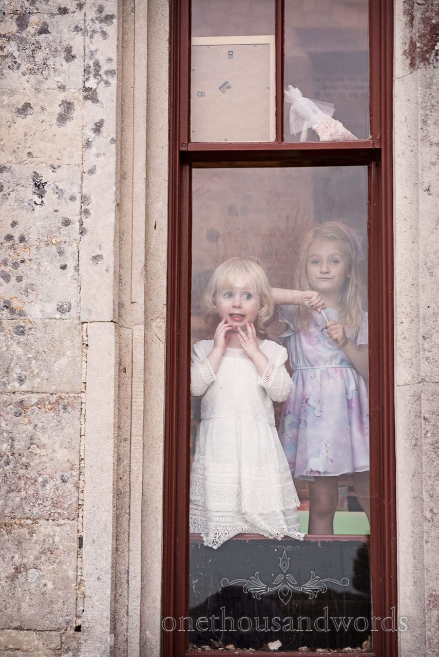 Flower girl looks out of window at sunset at Lulworth Castle Wedding venue