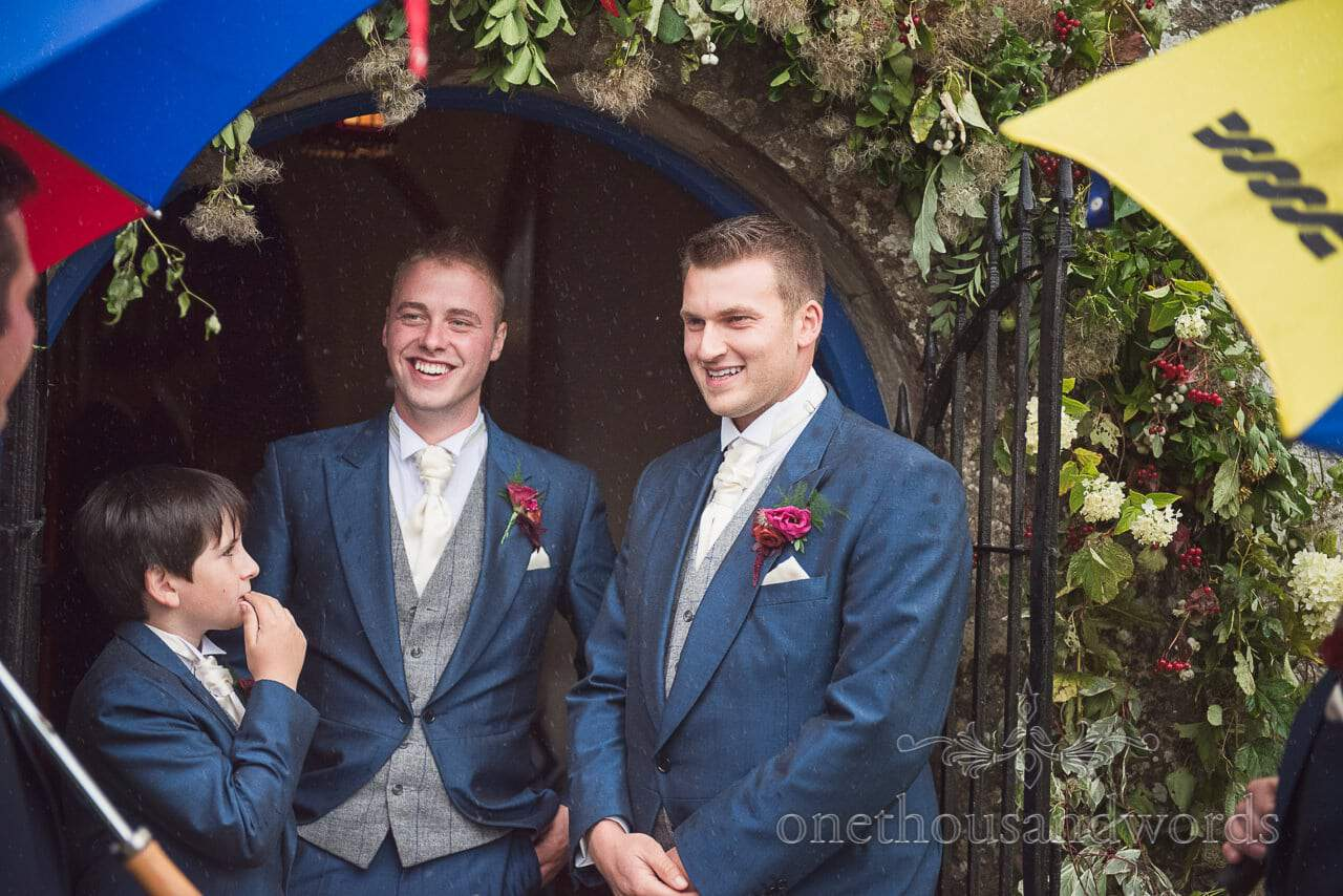 Groom and groomsmen in blue wedding suits shelter from the rain