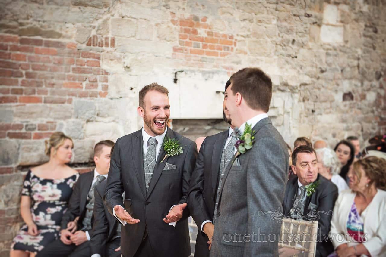 Groom and groomsmen share a joke at woodland Lulworth Castle wedding