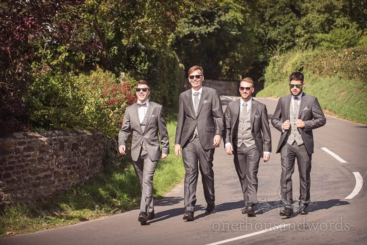 Groom and groomsmen walk to pub at woodland Lulworth Castle wedding