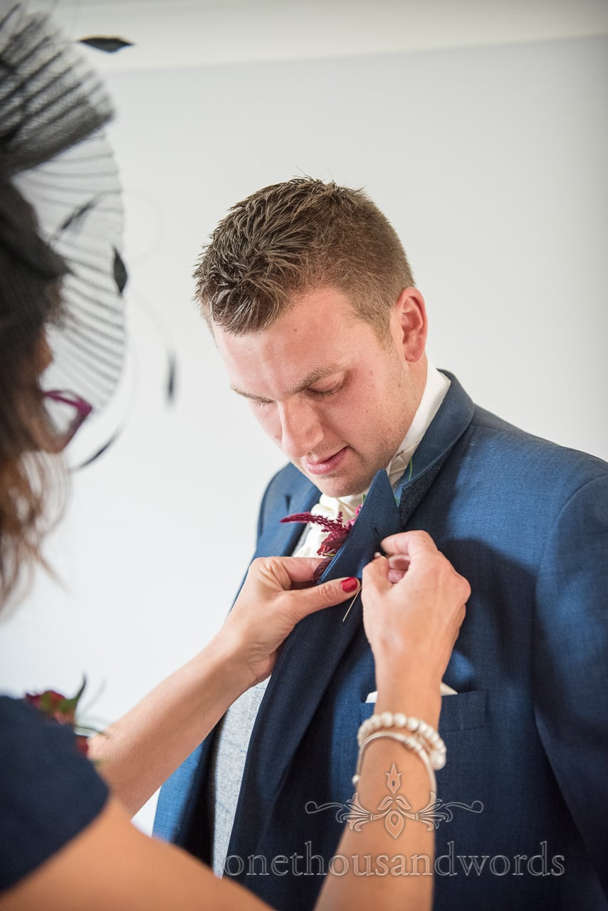 Groom has buttonhole pinned by mother before church ceremony