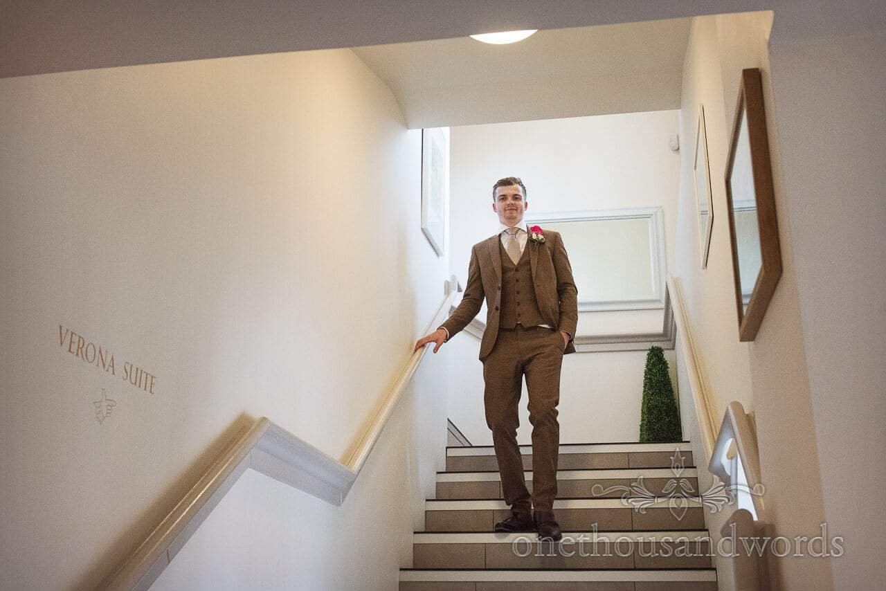 Groom in brown suit on staircase at Italian Villa