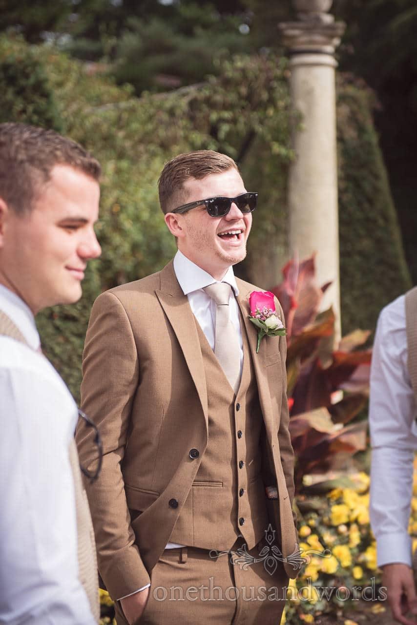 Groom in brown three piece suit laughs at Italian Villa wedding