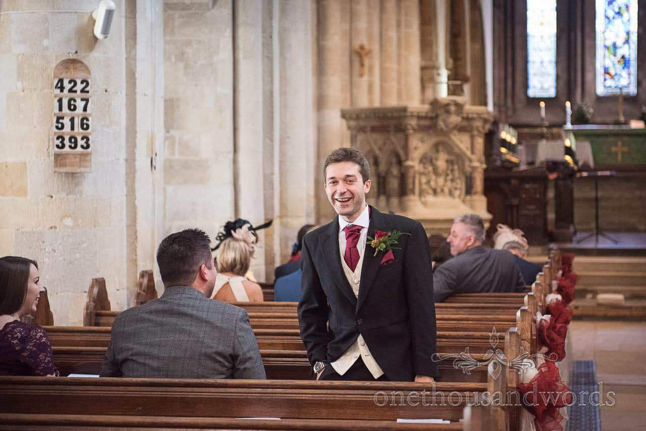 Groom jokes with wedding guests in Wimborne Minster wedding venue