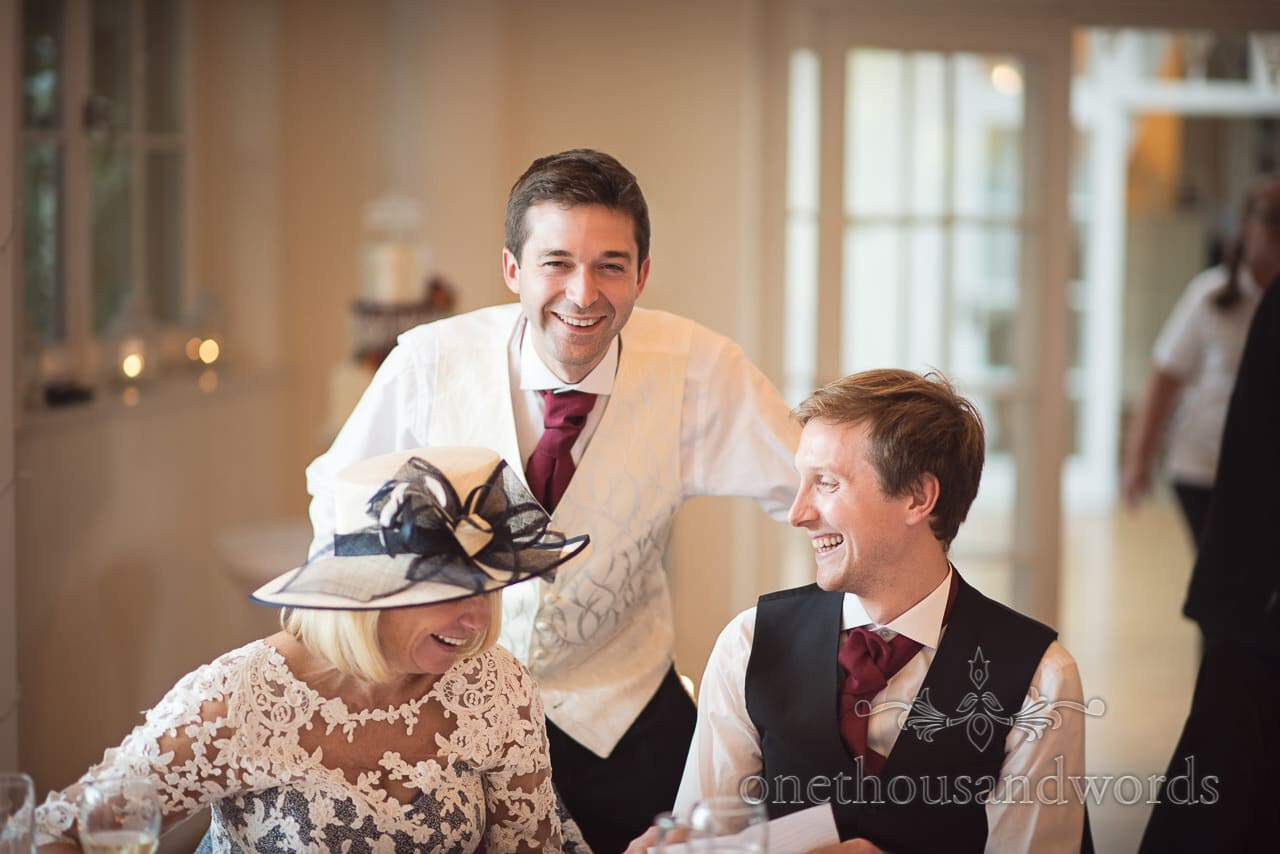 Groom laughs with his mother and best man at Hethfelton House