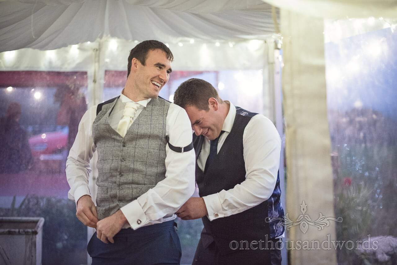 Grooms man is dressed by male wedding guest in wedding marquee
