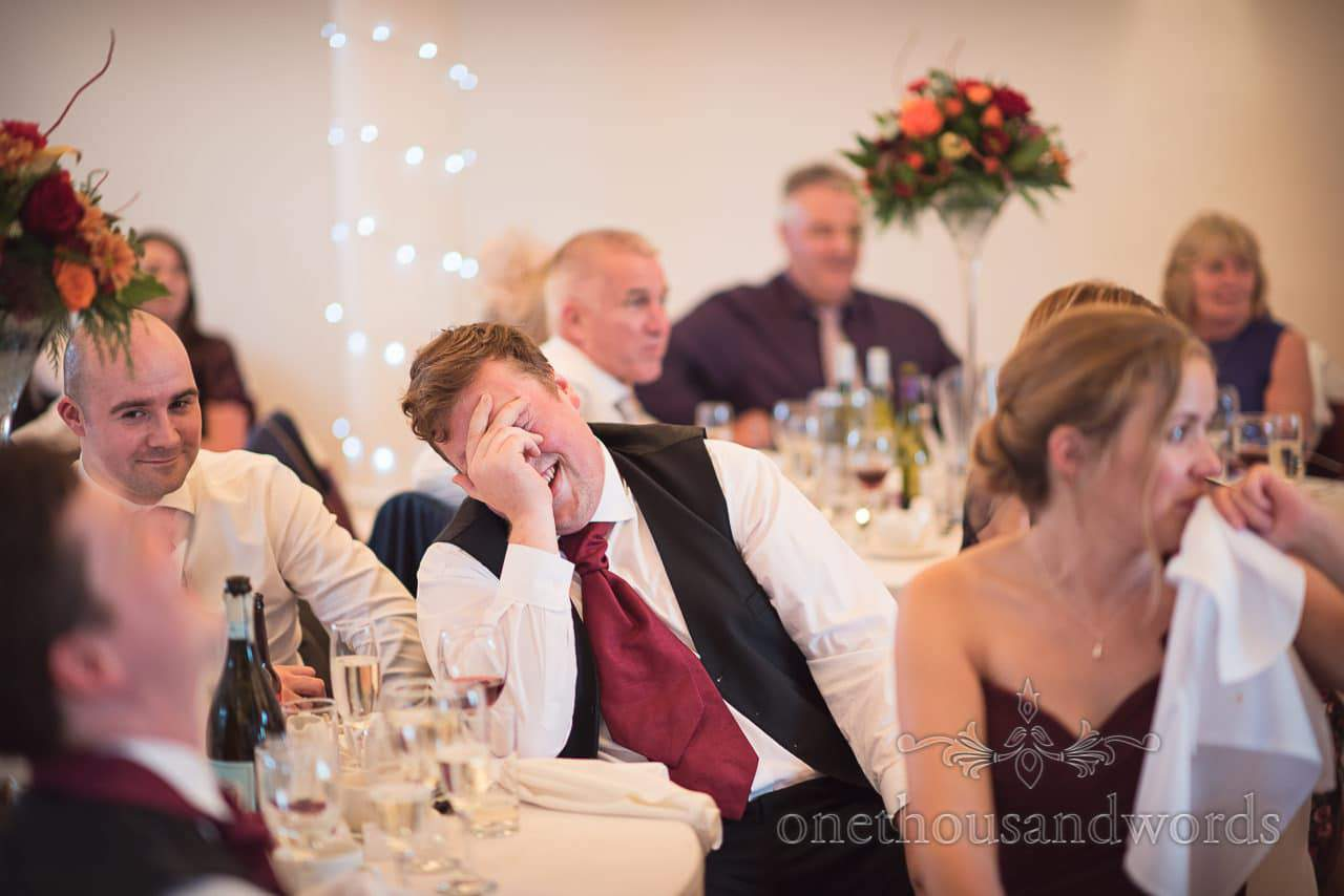 Groomsman collapses with laughter at Hethfelton House Wedding venue