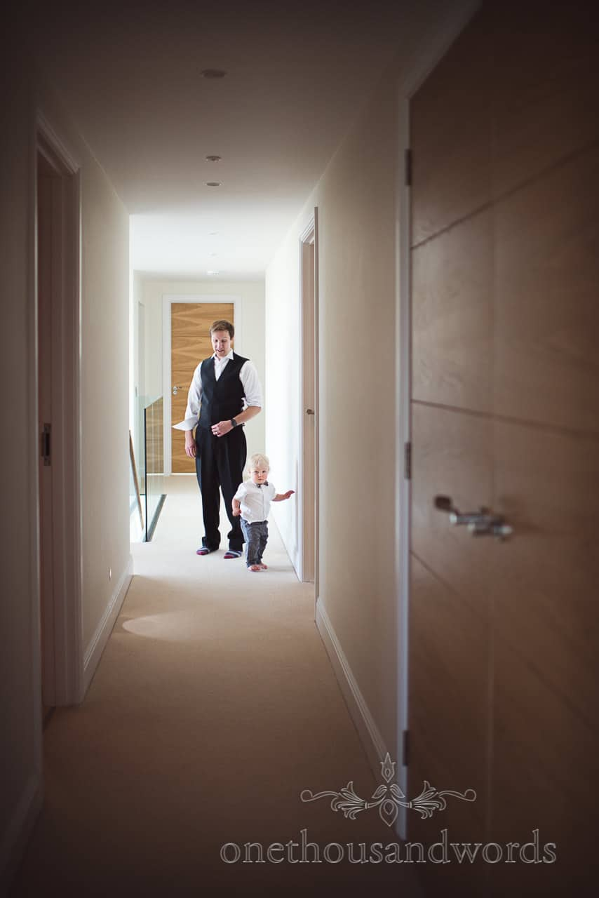 Groomsman with cute page boy in corridor during groom preparations