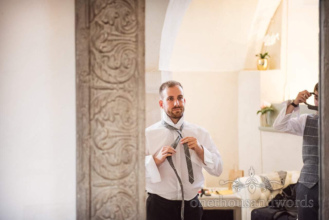 Groomsman getting ready in mirror at woodland Lulworth Castle wedding