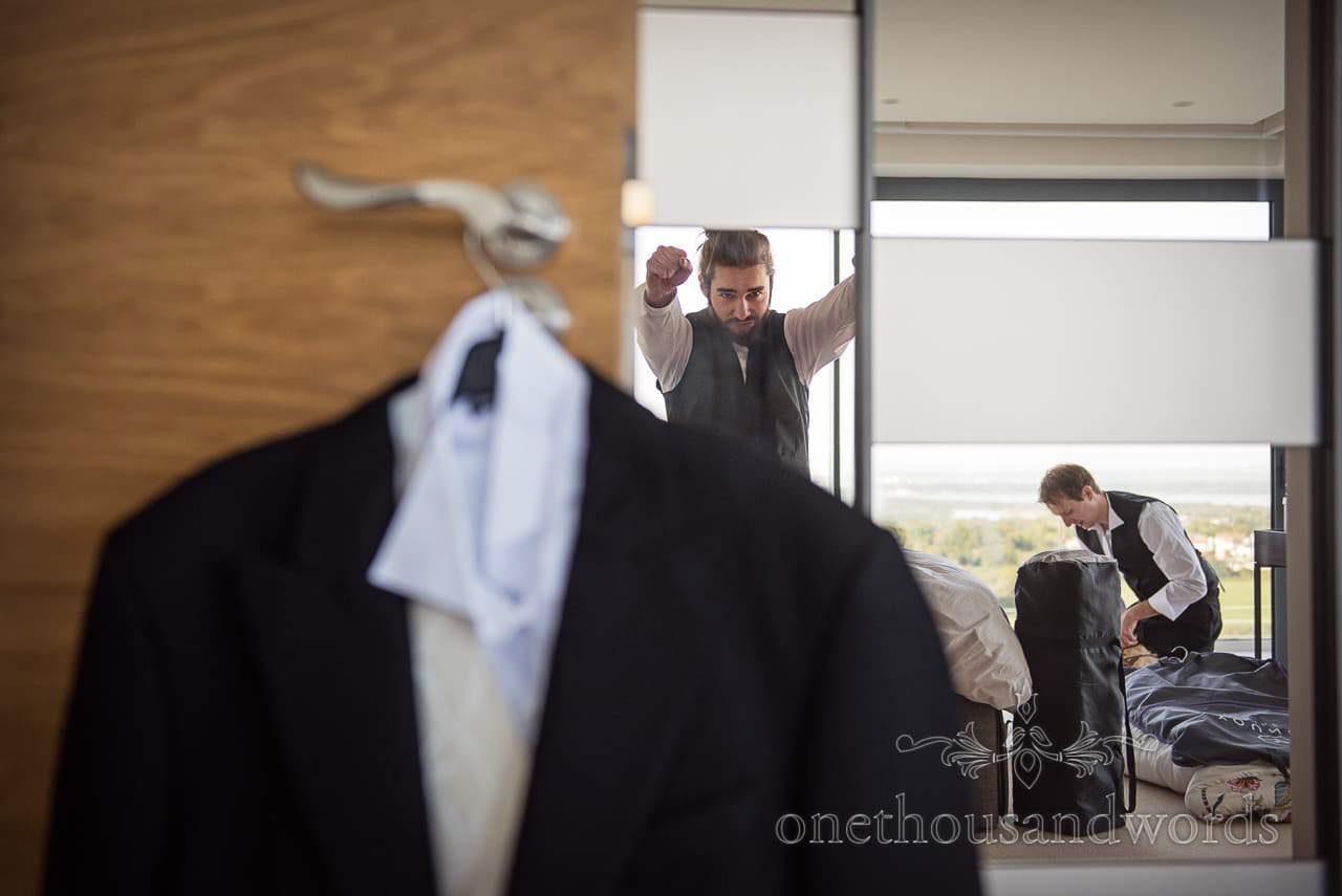 Groomsman in waistcoat stretches during wedding morning preparations