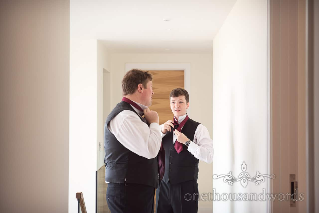 Groomsmen in black waistcoats tie red cravats on wedding morning