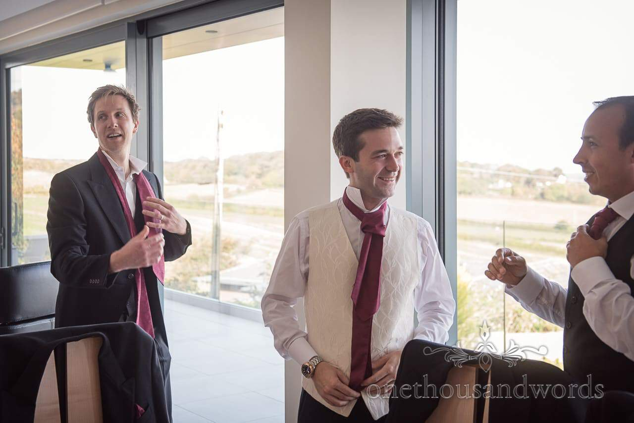 Groomsmen put on red cravats on wedding morning in Dorset