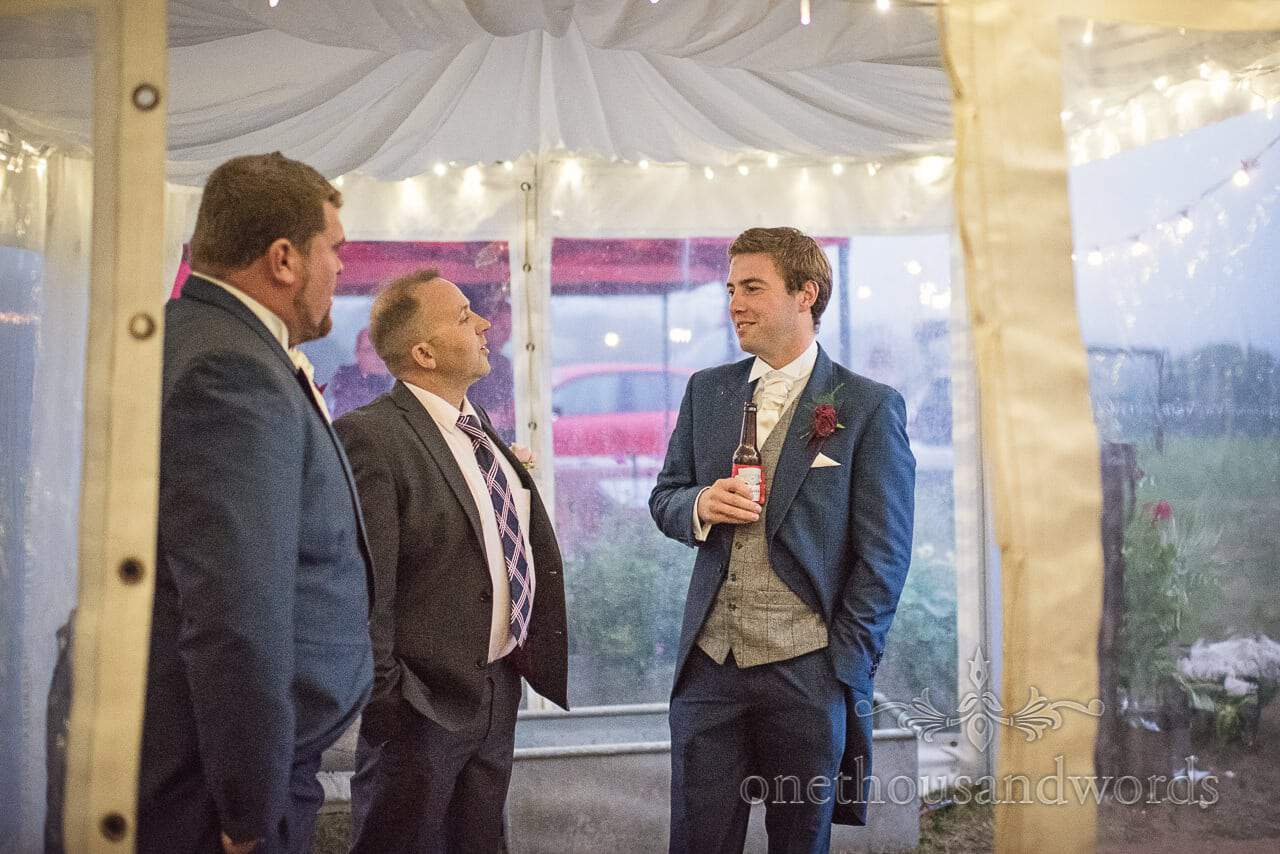 Groomsmen talk to guest with beers in wedding marquee entrance