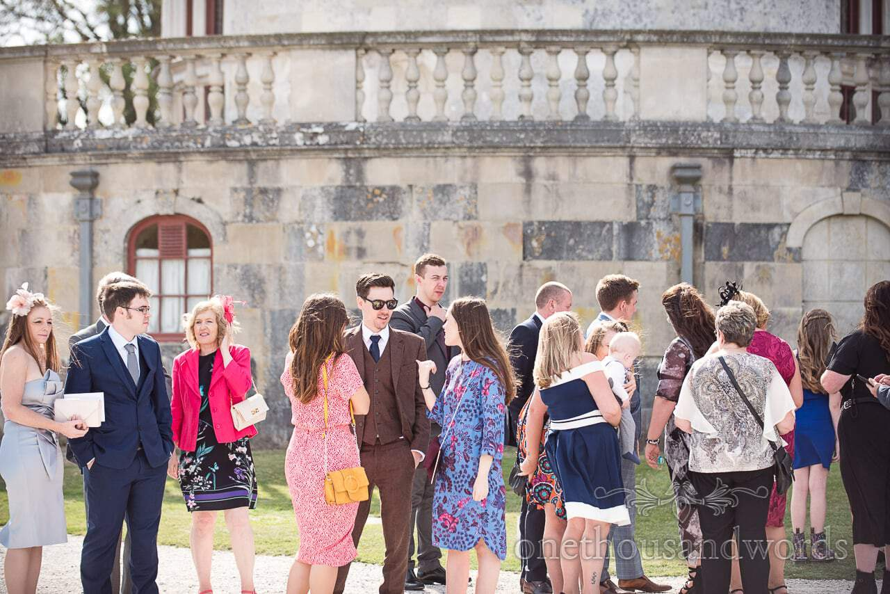 Guests gather in sunshine at woodland Lulworth Castle wedding