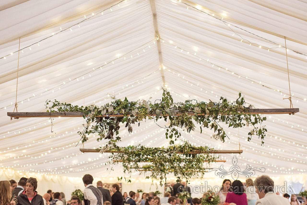Hanging ivy and flowers plank decorations at farm marquee wedding