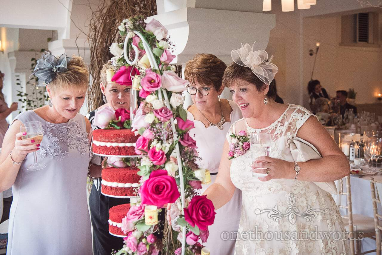 Italian Villa documentary wedding photos of mother of the groom with guests admiring cake