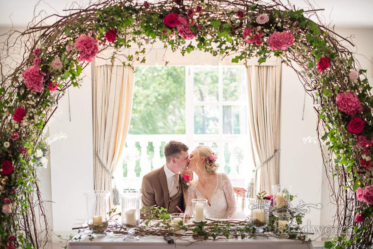 Italian Villa documentary wedding photos of newlyweds kissing beneath flower arch