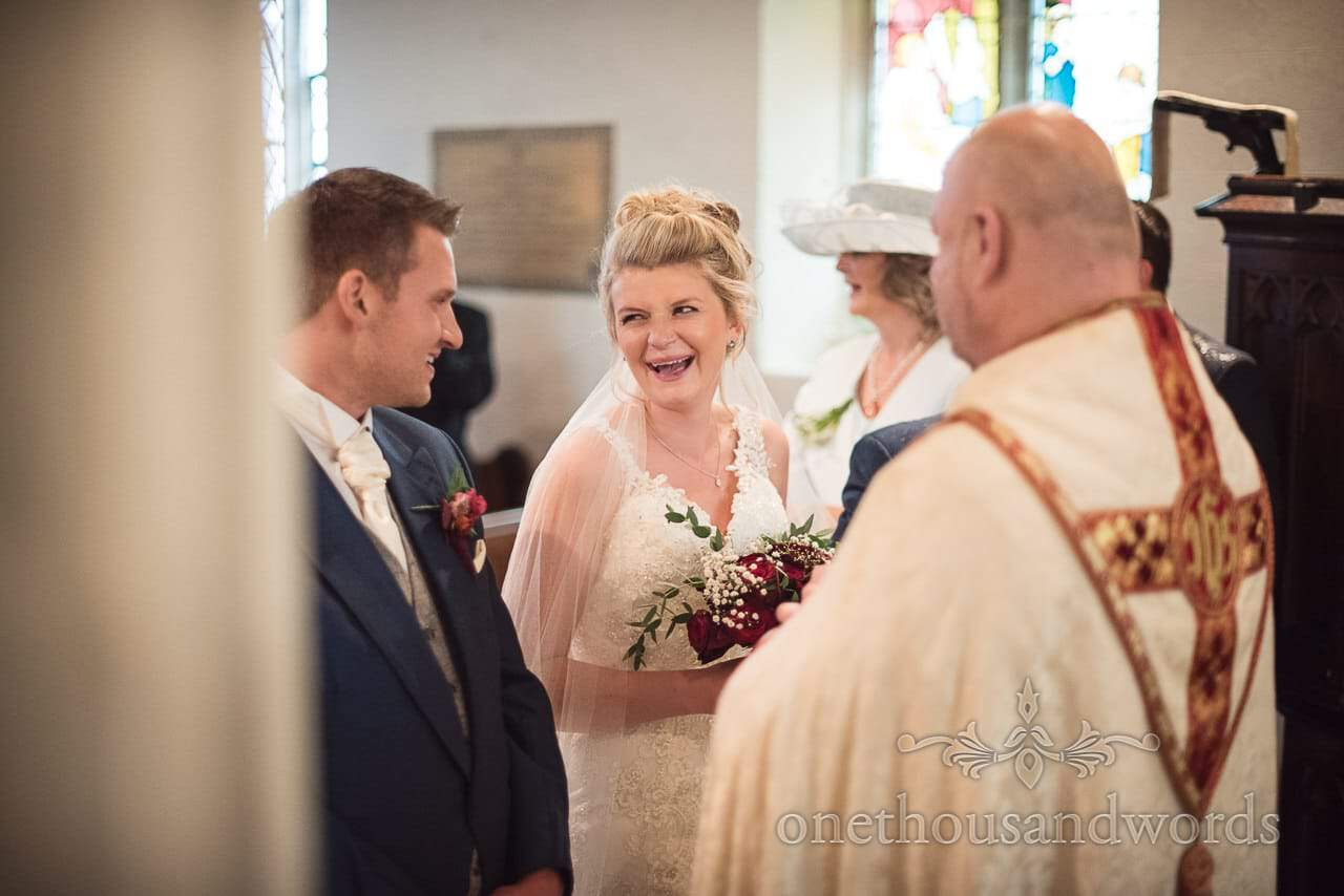 Laughing bride and groom during church wedding ceremony