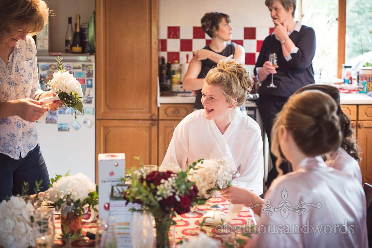 Laughing bride in kitchen on morning of farming wedding