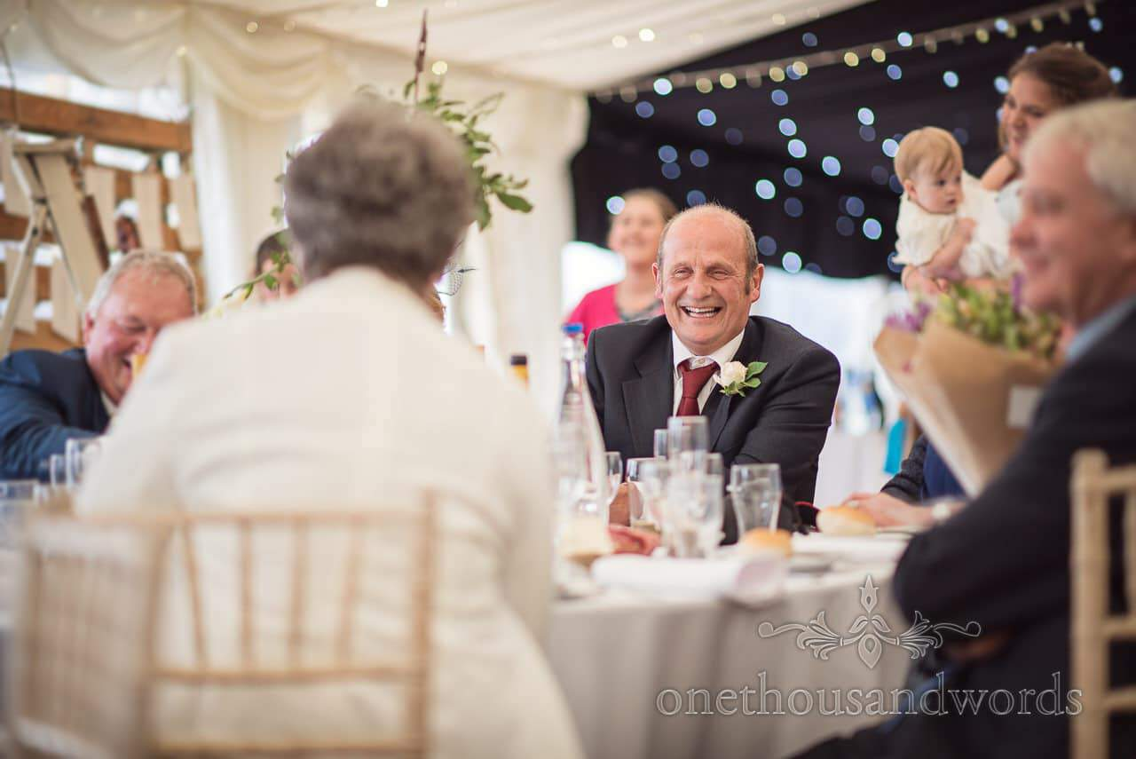 Laughing guest during speeches at farm marquee wedding