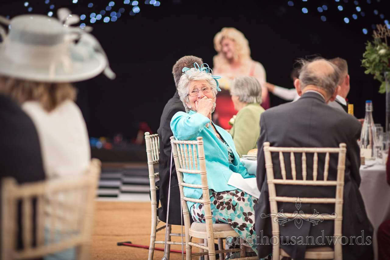 Laughing guest reaction during speeches at farm marquee wedding