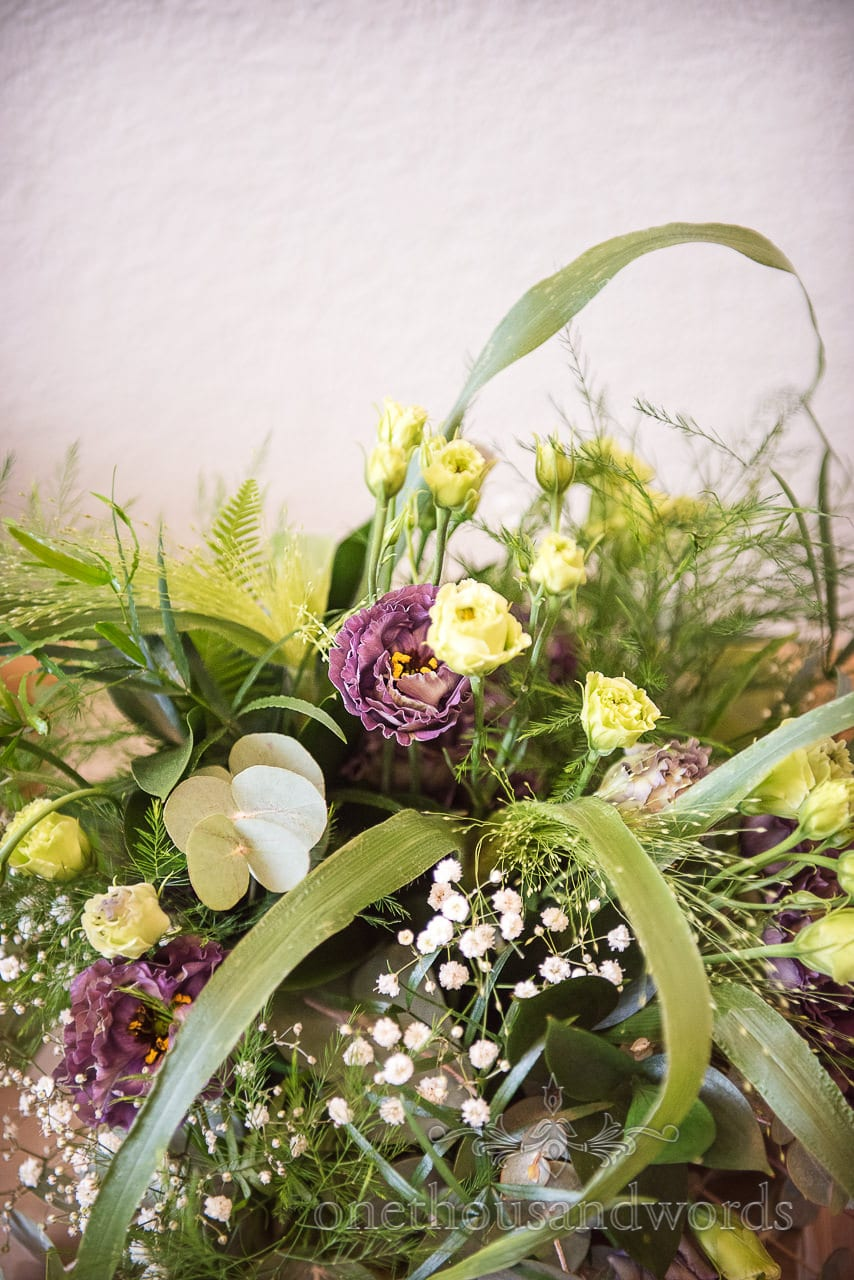 Lush green, purple and yellow bouquet from woodland Lulworth Castle wedding