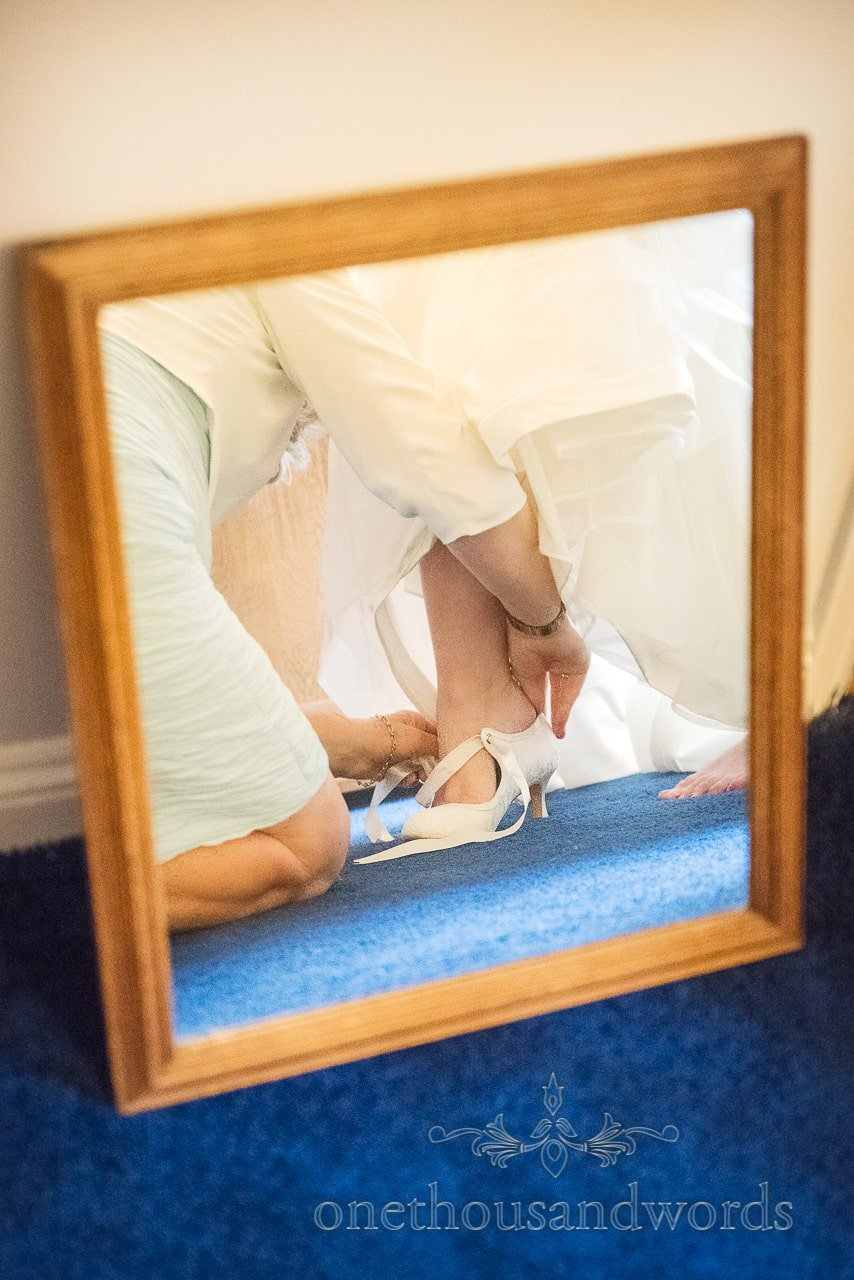 Mother of the bride helps with bridal shoes on wedding morning